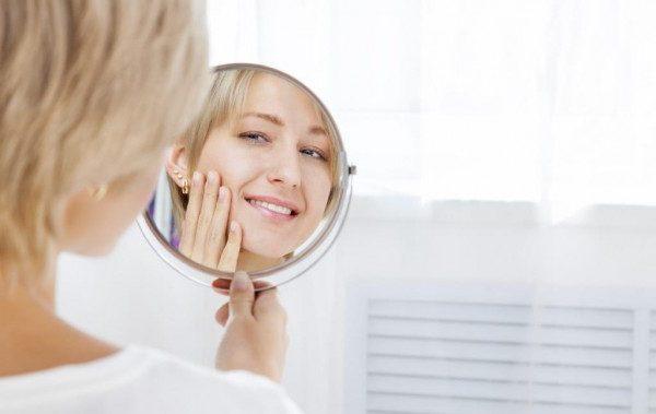 Девушка смотрит в зеркало лицо